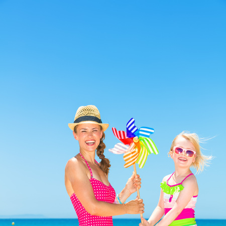 Photo for Portrait of smiling modern mother and daughter in bright beachwear on the beach holding colorful windmill toy - Royalty Free Image