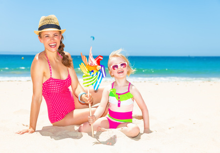 Photo for smiling modern mother and daughter in bright beachwear on the seashore with colorful windmill toy - Royalty Free Image