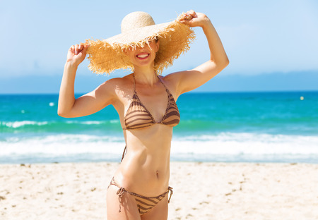 Photo for Blue sea, white sand paradise. young woman in bikini and beach straw hat on the seacoast - Royalty Free Image