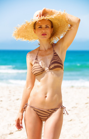 Photo for Blue sea, white sand paradise. Portrait of modern woman in beachwear and straw hat on the seashore - Royalty Free Image