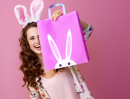 Photo for Festive bunny and eggs season. happy modern woman in Easter bunny ears isolated on pink hiding behind Easter shopping bag - Royalty Free Image