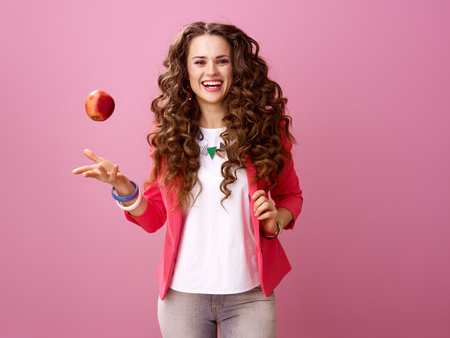 Photo pour Pink Mood. smiling trendy woman with long wavy brunette hair on pink background throwing up an apple - image libre de droit