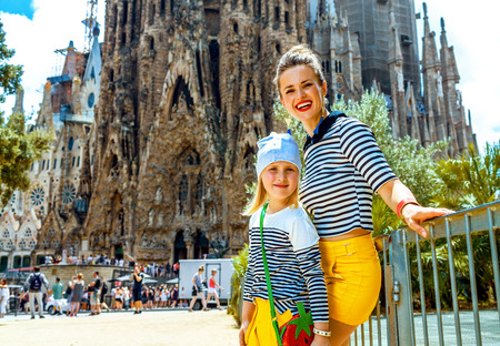 Foto de Barcelona - July, 10, 2017: Portrait of young mother and daughter travellers against Sagrada Familia in Barcelona, Spain - Imagen libre de derechos