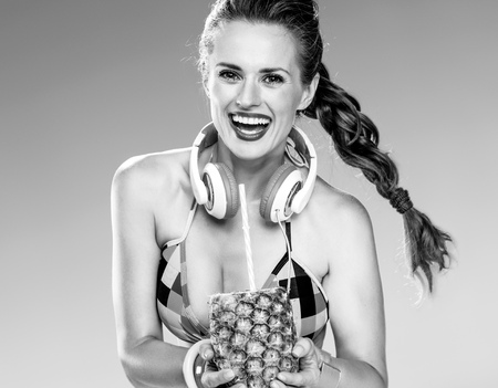 Photo for Perfect summer. happy young woman with headphones wearing colorful beachwear on the beach showing refresh summer cocktail in pineapple - Royalty Free Image
