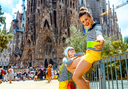 Foto de Barcelona - July, 10, 2017: modern mother and child travellers near Sagrada Familia in Barcelona, Spain with smartphone taking selfie - Imagen libre de derechos