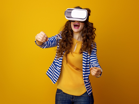 Foto de smiling stylish woman with long wavy brunette hair isolated on yellow wearing cardboard VR glasses and driving - Imagen libre de derechos