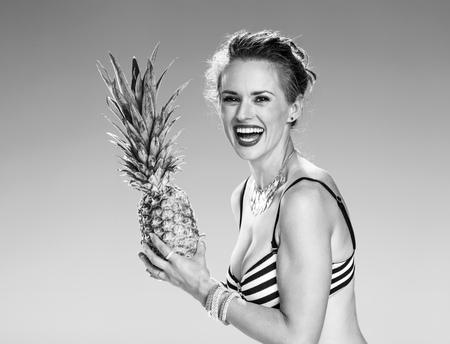 Photo for Perfect summer. Portrait of smiling young woman in swimwear on the seacoast with pineapple - Royalty Free Image