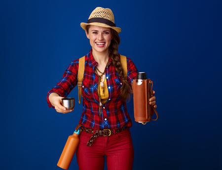 Photo pour Searching for inspiring places. smiling active woman hiker in a plaid shirt proposing a hot beverage from a thermos bottle isolated on blue - image libre de droit