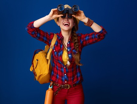 Foto de Searching for inspiring places. happy fit tourist woman with backpack looking up through binoculars on blue background - Imagen libre de derechos