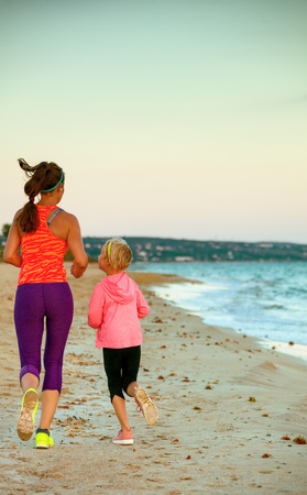 Photo for Look Good and feel great. Seen from behind young mother and daughter in sport style clothes on the seacoast in the evening jogging - Royalty Free Image