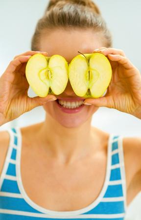 Foto de Happy young woman holding two slices of apple in front of eyes - Imagen libre de derechos