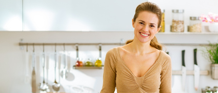 Foto de smiling young housewife in modern kitchen - Imagen libre de derechos