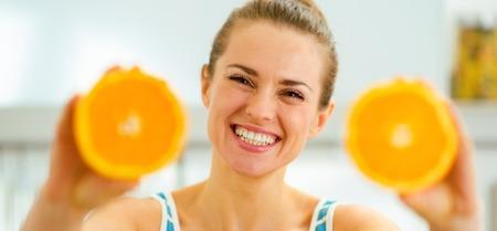Foto de Happy young woman showing slices of orange - Imagen libre de derechos