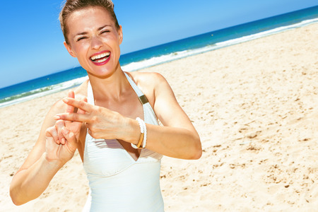 Photo for Fun on white sand. smiling modern woman in swimwear on the seashore showing hashtag gesture - Royalty Free Image
