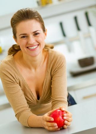 Foto de happy young housewife with apple in modern kitchen - Imagen libre de derechos