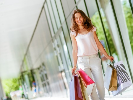 Foto de Happy young woman with shopping bags walking on the mall alley - Imagen libre de derechos