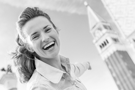 Foto de Happy young woman pointing on campanile di san marco in venice, italy - Imagen libre de derechos