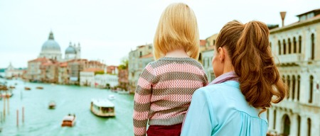 Foto de Mother and baby girl standing on bridge with grand canal view in venice, italy. rear view - Imagen libre de derechos