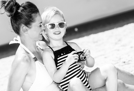 Photo for Family fun on white sand. happy modern mother and child in swimwear on the beach viewing photos on camera - Royalty Free Image