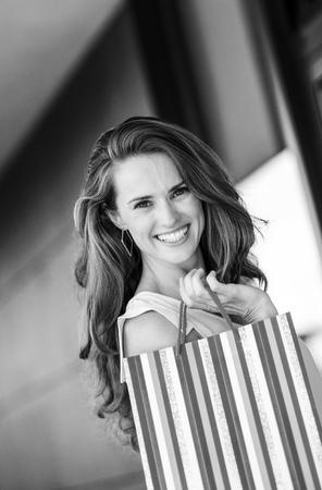 Foto de smiling young woman with shopping bag - Imagen libre de derechos
