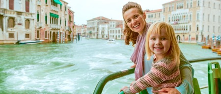 Foto de Happy mother and baby girl travel by venice water bus - Imagen libre de derechos
