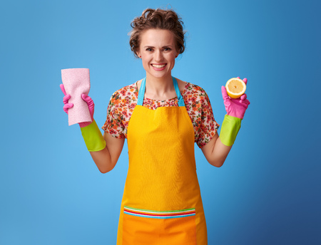 Photo pour Big cleaning time. smiling young housewife with rubber gloves holding half a lemon and cleaning cloth isolated on blue background - image libre de droit