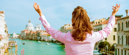 Foto de Happy young woman standing on bridge with grand canal view in venice, italy - Imagen libre de derechos