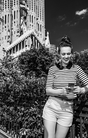 Foto de legant traveller woman in yellow shorts and stripy shirt in Barcelona, Spain writing sms - Imagen libre de derechos