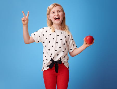 Photo pour happy modern child in red pants with an apple showing victory gesture on blue background - image libre de droit