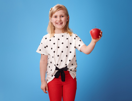 Photo pour smiling modern girl in red pants showing an apple on blue background - image libre de droit