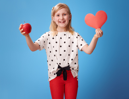 Photo pour smiling modern child in red pants showing a paper heart and an apple on blue background - image libre de droit