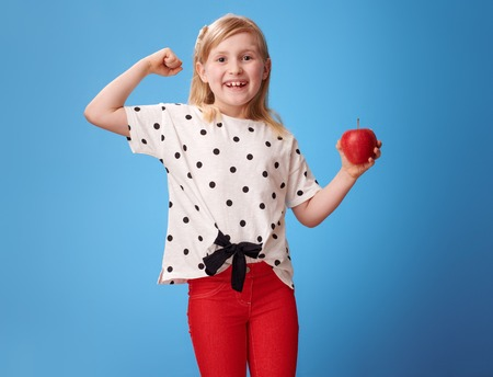 Photo pour smiling modern child in red pants with an apple showing biceps against blue background - image libre de droit