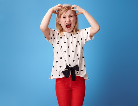 Foto de furious modern child in red pants scratching head isolated on blue background - Imagen libre de derechos