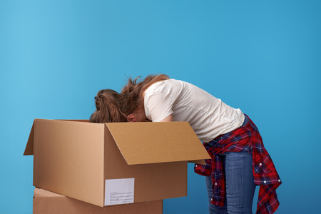 Photo pour modern hipster in white shirt looking for something in the a cardboard box against blue background - image libre de droit
