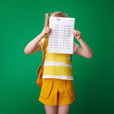 Photo for pupil with backpack hiding behind a bad grade test on green background - Royalty Free Image