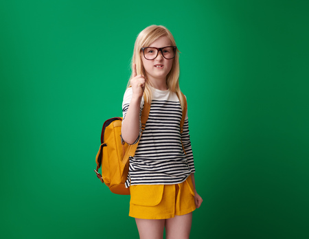 Foto de annoyed pupil with backpack threatening with finger against green background - Imagen libre de derechos