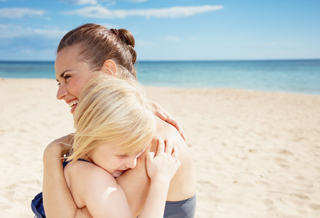 Photo for Smiling young mother and daughter in beachwear on the seacoast hugging - Royalty Free Image