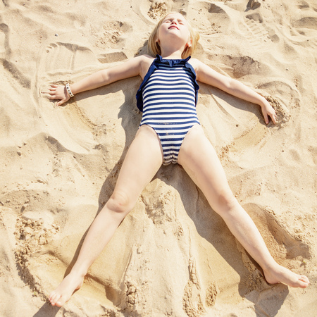 Photo for Relaxed child in beachwear laying on sand and making angel on the beach - Royalty Free Image