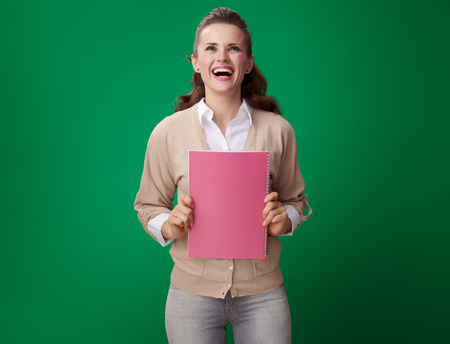 Foto de smiling young student woman with pink notebook with pink notebook against green background - Imagen libre de derechos