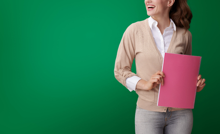 Foto de happy young student woman with pink notebook looking at copy space isolated on green background - Imagen libre de derechos