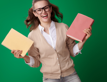 Foto de smiling young student woman with books isolated on green background - Imagen libre de derechos