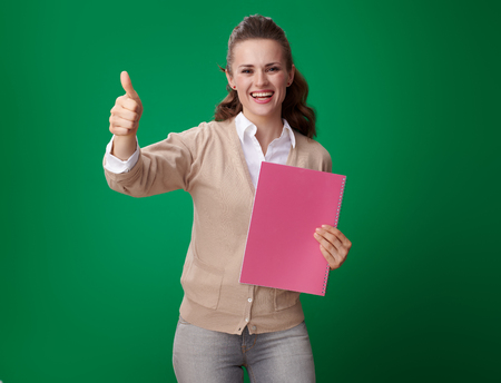 Foto de happy modern student woman with pink notebook showing thumbs up against green background - Imagen libre de derechos