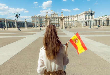 Photo for Seen from behind modern traveller woman with Spain flag against Royal Palace - Royalty Free Image