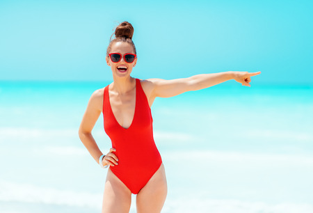 Photo for smiling young woman in red beachwear on the seashore pointing at something - Royalty Free Image