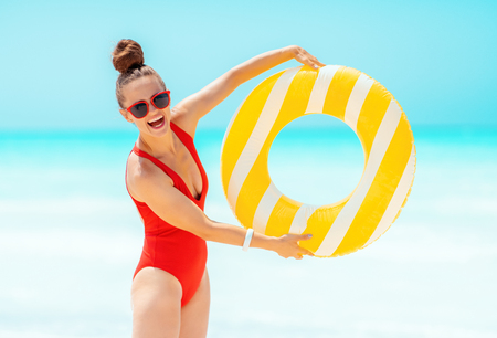 Photo for happy young woman in red beachwear on the beach showing yellow inflatable lifebuoy - Royalty Free Image