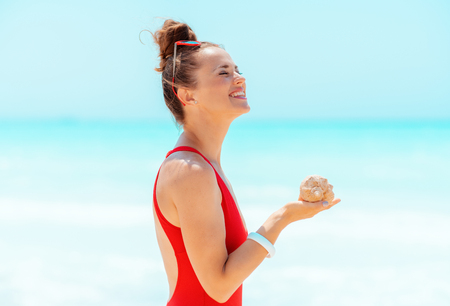 Foto de smiling modern woman in red swimsuit with sea shell on the beach - Imagen libre de derechos