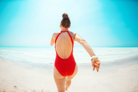 Photo for Seen from behind modern woman in red beachwear on the seashore jogging - Royalty Free Image