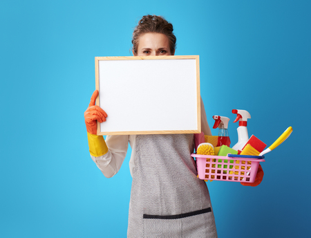 Photo for young cleaning lady in apron with a basket with detergents and brushes looking out from blank board isolated on blue background. Cleaning service worker shows the price list of cleaning prices. - Royalty Free Image