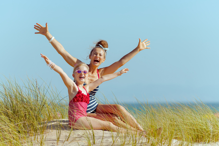 Photo for happy modern mother and child in beachwear on the beach rejoicing. getting vitamin D after long winter months. modern сaucasian mother 30 something years old in white blue striped swimsuit brunette. - Royalty Free Image