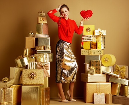 Photo for Full length portrait of cheerful stylish woman in red blouse and golden sparkly sequin pencil skirt with red heart among 2 piles of golden gifts in front of a plain wall. Valentine's Day. - Royalty Free Image